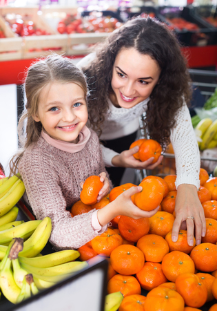 Joyful young woman and smiling little daughter purchasing sweet tangerines at market. Focus on girl