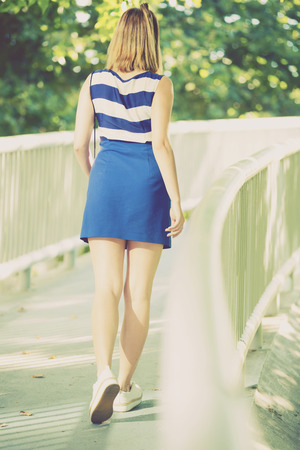 Back view of cute young girl in dress walking on bridge in city park Stock Photo