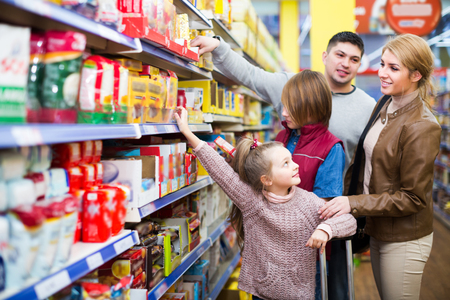 store shelf: Ordinary positive family with children buying groceries in supermarket Stock Photo