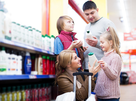 store shelf: Smiling middle-class family of four selecting shower gel in shop Stock Photo