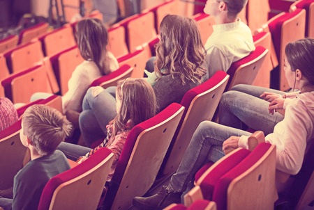 Cheerful group expecting movie to begin in cinema