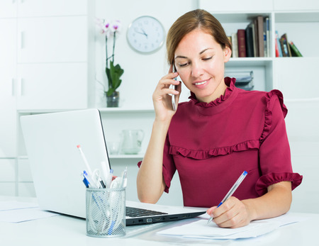 young attractive female employee answering on phone and taking notes at office