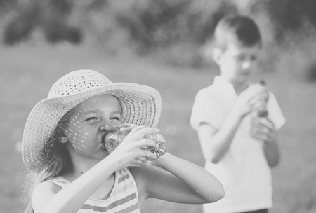 happy girl in elementary school age drinking water from plastic bottle outdoors Stock Photo