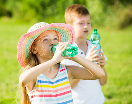 portrait of glad girl holding plastic bottle with water outdoors on summer day Stock Photo