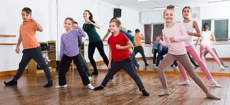 Cheerful children studying contemp dance in dancing studio