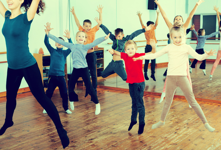 Glad little children studying modern style dance in class Stock Photo