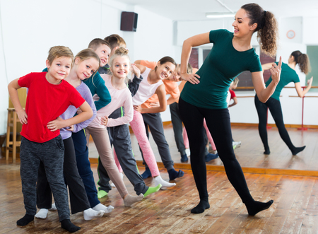Cheerful boys and girls studying contemp dance in dancing studio