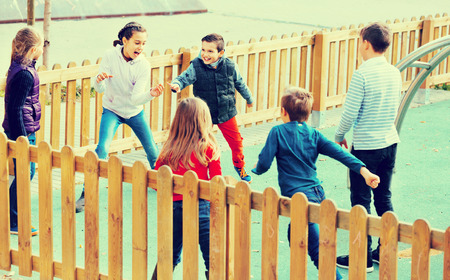 romp: Group of happy cheerful  children playing romp game Touch-last outdoors Stock Photo