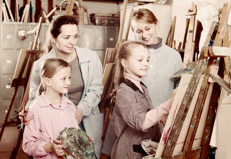 happy american skillful young students looking at progress of fellow student during painting class Stock Photo