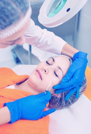 Doctor de la mujer que hace la inyección de belleza al cliente femenino positivo alegre