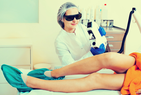 Young  smiling female client doing laser hair removal from legs