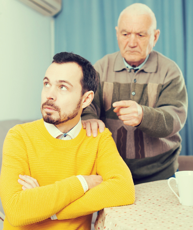 Mature father having disagreement with adult son at home