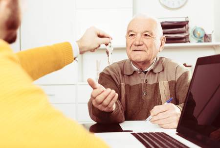 Elderly man and young agent sign lease contract of apartment at office and hand over keys