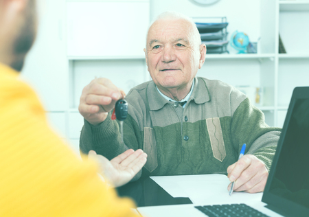 vise: Elderly man and young manager sign car purchase contract and hand over keys