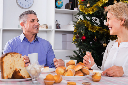 Cheerful positive mature couple having breakfast at festive Christmas table