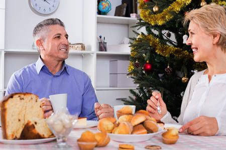 Cheerful positive mature couple having breakfast at festive Christmas table