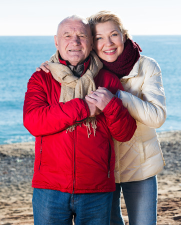 Mature man and woman walking by sea on sunny day Stock Photo