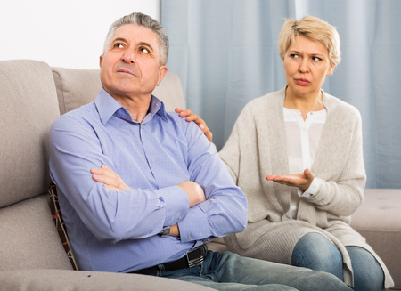 Woman and man 51-56 years old are offended at each other because of the misunderstanding in his home.