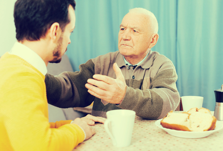 eldest: Elderly father teaches and instructs his son at table at home