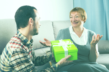 Adult son presenting gifts to mature mother during evening together at home