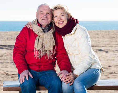 Mature man and woman sitting comfortably on bench by sea Stock Photo