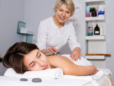 Young female client enjoying relaxing massage in beauty salon