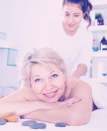 clientes de sexo femenino mayor que disfruta de masaje relajante en salón de belleza Foto de archivo
