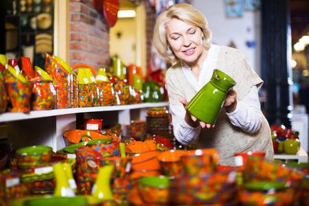 utensilios de cocina: Elderly blonde female chooses ceramic ware in the cookware section at hypermarket