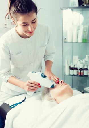 visitante femenino maduro que hace procedimientos de la belleza para la cara en salón del balneario