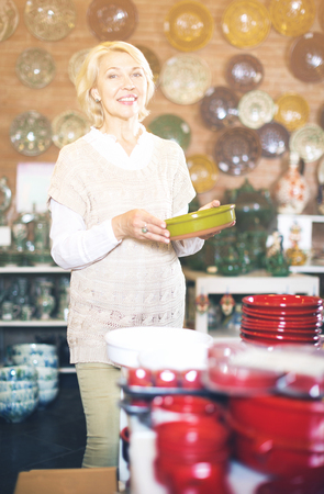 Glad senior woman posing with ceramic tableware at workshop Stock Photo