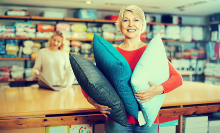 The senior seller is showing wide assortment of pillows in a textile store.  Stock Photo