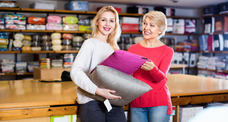 boasting: Happy girl and mature woman customers showing bought pillows in home textile shop