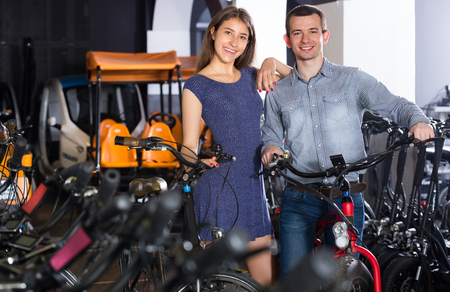25s: Portrait of positive guy and girl looking for  bikes ot rental store  indoors Stock Photo
