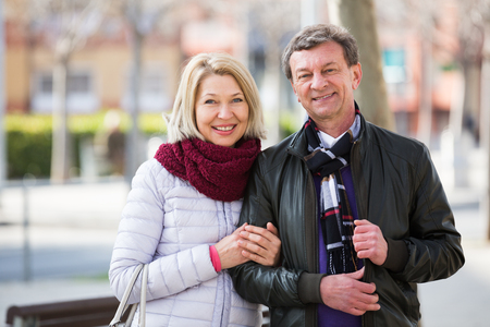 Loving mature man and woman having walk together in spring