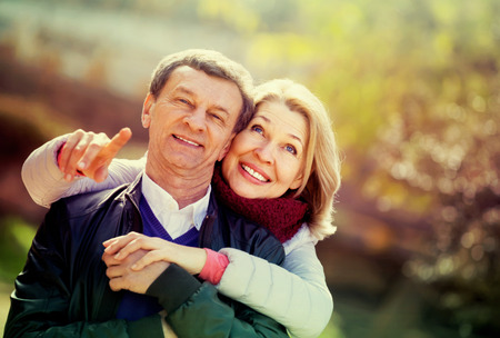 Portrait of smiling mature spouses enjoying spending time at spring park. Focus on woman