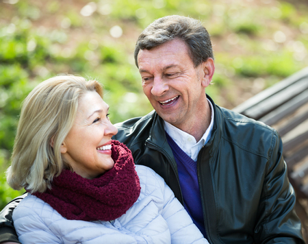 snuggle: Portrait of smiling aged couple enjoying spring day on the bench in park . Focus on man