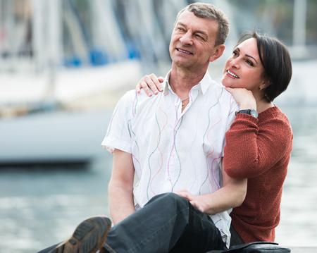 Portrait of happy loving mature couple resting against water landscape