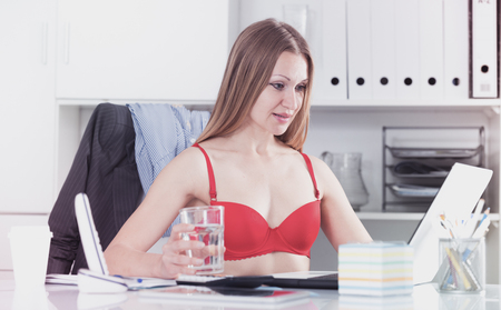 Sexy business woman wearing red bra in workplace in hot office