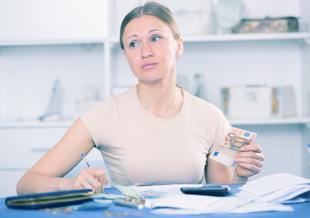 indebtedness: Woman sitting at table at home with calculator counting money for paying bills