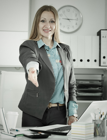 communicable: Successful businesswoman standing in office with open hand ready for handshake Stock Photo