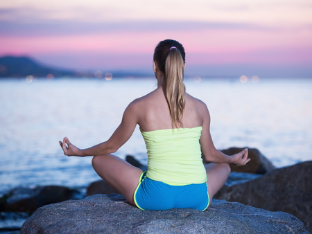 positive sportwoman meditating in yoga asana padmasana in evening outdoor