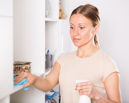Smiling woman wiping dust on shelves of cabinet at home Stock Photo