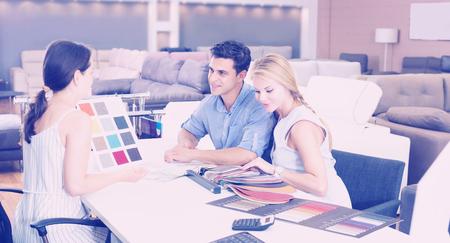 Paar dat overleg met de assistent over de keuze van een kleur voor een nieuwe bank