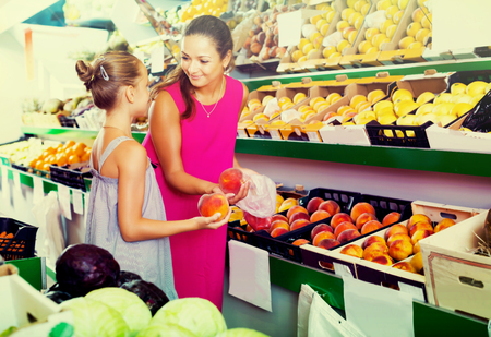 Glad woman with daughter picking peaches in fruit section in supermarket Stock Photo