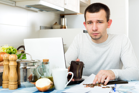 Sad man with laptop at table in home interior Stock Photo