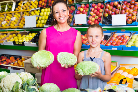Portrait of smiling mother with girl picking fresh cole at food store. Focus on both persons Stock Photo