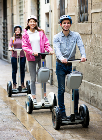 Positve girls and guy traveling through city by segways