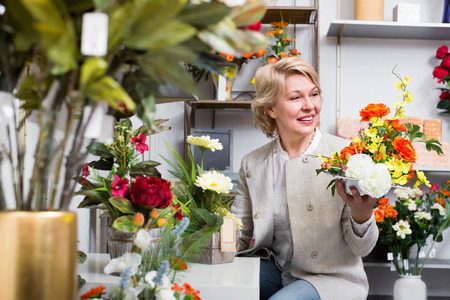 Happy positive  mature blond woman selecting flowers in store