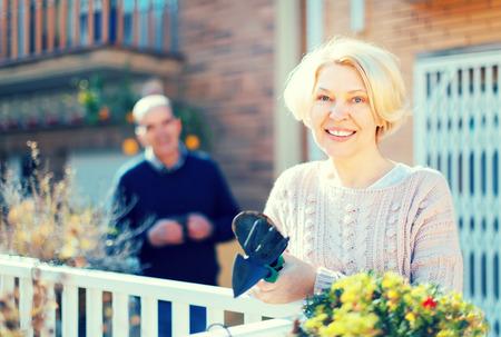 Hogere vrouw met het tuinieren toebehoren op een terras dichtbij haar huis met haar echtgenoot die een kop van koffie op een achtergrond houden Stockfoto