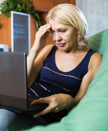 Crying elderly woman receiving bad news in internet Stock Photo